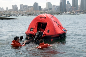 SAN DIEGO Ð San Diego area Sea Scouts climb into a life raft as part of a survival swim during Safety at Sea Day hosted by Coast Guard Sector San Diego, April 23, 2011.  The event included stations that taught firefighting, knot tying, plugging and patching and a survival swim. U.S. Coast Guard photo by Petty Officer 2nd Class Henry G. Dunphy.