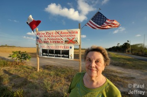 Pamela Taylor stands by a sign she erected to protest the construction of the border wall along the U.S.-Mexico border. Taylor's home, outside Brownsville, Texas, is being stranded outside the wall, which she and other critics believe is being constructed not to control illegal immigration but rather to enrich politically-connected construction companies.